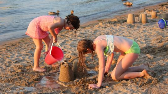 Girls build a sandcastle at the water's edge