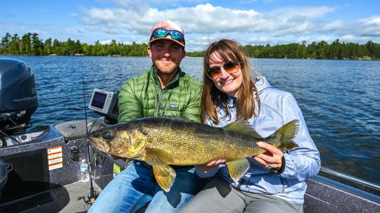 Fishing guide and client holding walleye