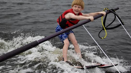 Young boy smiling as he learns how to water ski