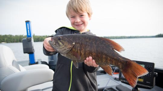 Young boy proudly holding a bass