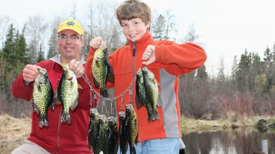 Farther and son with a stringer of crappies