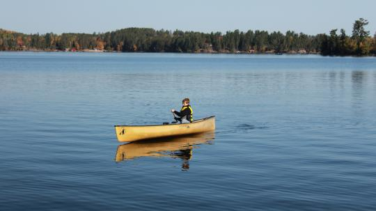 Boy solo-paddling a canoe on Lake Vermilion