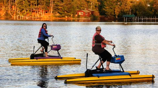 Two women hydro-biking at sunset