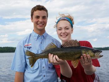 Brother and sister fisherpeople show off a perfect walleye