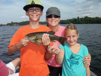 A family smiles with a bass on Lake Vermilion
