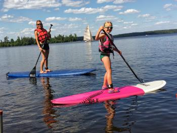 A mother and daughter enjoy the stand up paddle boards