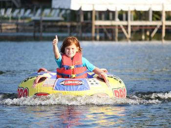 Girl enjoys tubing on a sunny day on Lake Vermilioin