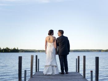 Bride and groom on a dock at Pehrson Lodge