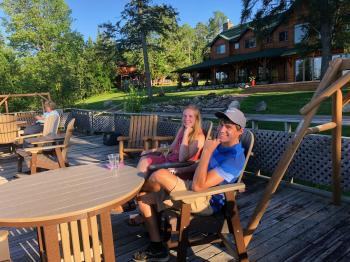 Couple enjoys a glass of wine on the Sun Deck at Pehrson Lodge