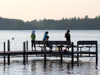 A family fishes from the dock at Pehrson Lodge