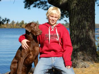 A boy and his dog in the yard of Aurora, pet-friendly cabin