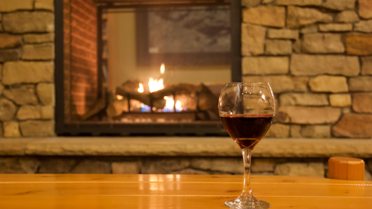 Glass of wine by the fireplace at Pehrson Lodge during fall.