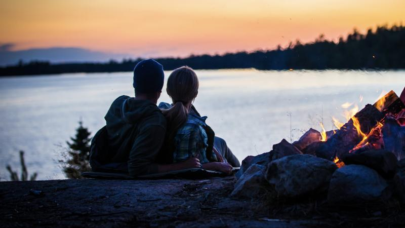 Couple sitting by the fire on Lake Vermilion at sunset.