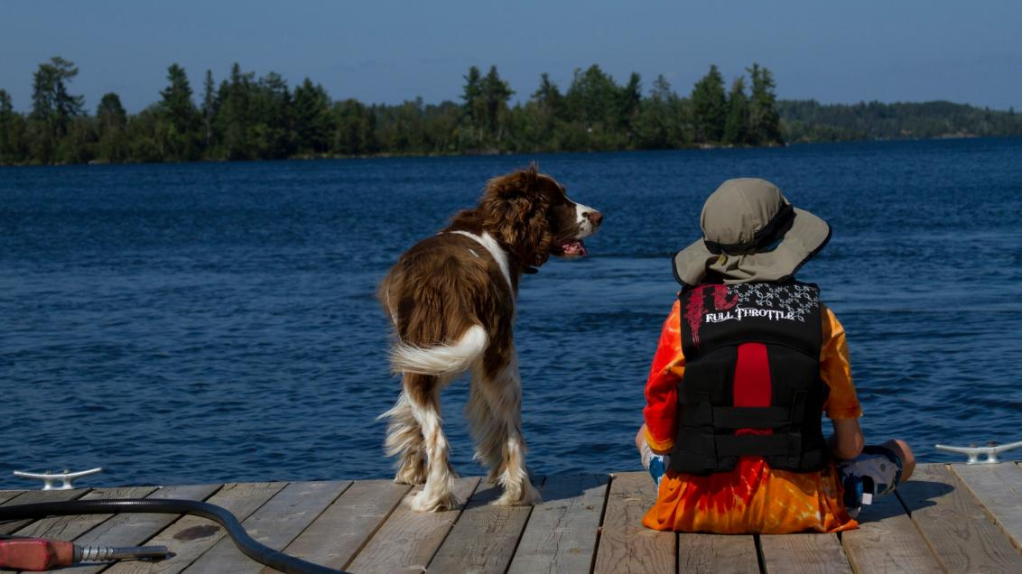 Boy and dog sitting on the dock